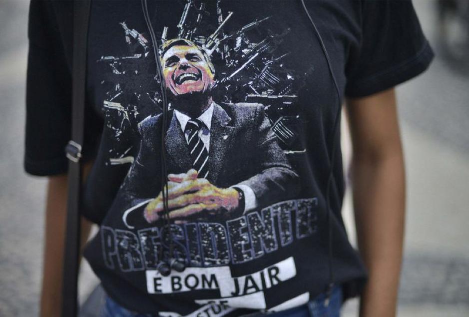 29 de setembro de 2018, Brasil, Rio de Janeiro: Um defensor do candidato presidencial de extrema direita Bolsonaro está vestindo uma camiseta com sua foto em um comício.